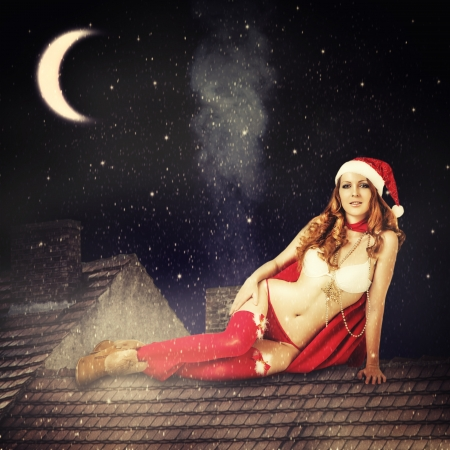 beautiful sexy christmas fairy woman  in red stockings, lingerie and in santa hat sitting on tiled roof of house at magic night photo
