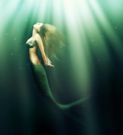 판타지. 물고기 꼬리와 물 아래 바다에서 긴 개발 머리 수영을 가진 아름 다운 여자의 인어 스톡 콘텐츠