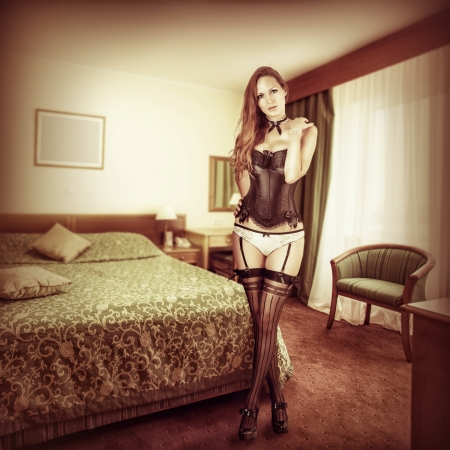 sexy legs stockings: Sexy beautiful woman in seductive lingerie - black corset, stockings and panties in bedroom Stock Photo