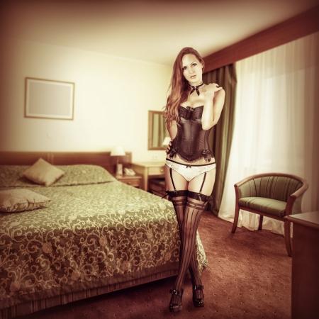 herrin: Sexy schöne Frau in verführerischen Dessous - schwarzes Korsett, Strümpfe und Unterhosen im Schlafzimmer Lizenzfreie Bilder