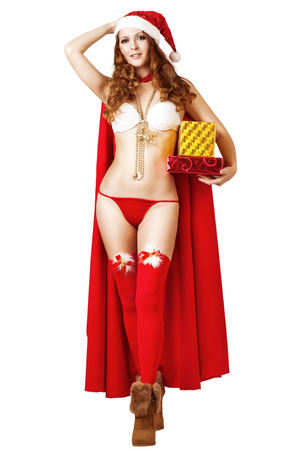 Sexy christmas woman wearing  bikini and red santa claus hat holding gift boxes isolated on white  photo