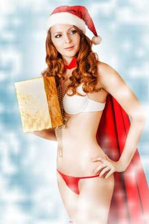 Sexy christmas woman wearing bikini and red santa claus hat holding golden gift box on snow whiteand blue   photo