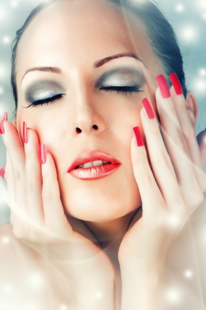Winter Skin Care. Beautiful female face with red lips and long lashes. Long false nails photo