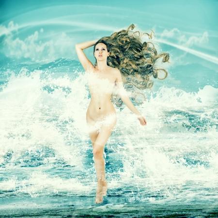afrodita: Hada atractiva mujer delgada con el pelo largo y rizado - Aphrodite se encuentra en el agua de mar en un aerosol de las olas del mar