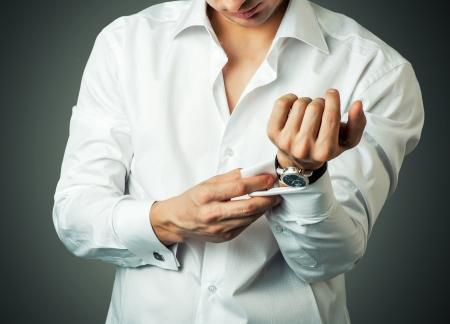 Sexy man knopen manchet-link op de Franse manchetten mouwen luxe witte overhemd Stockfoto