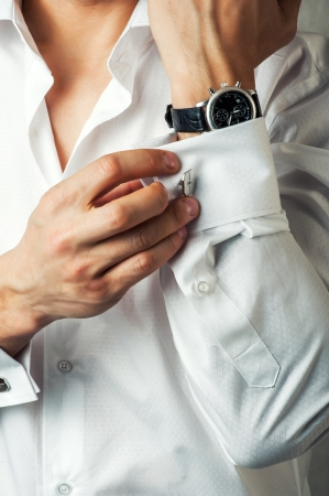 suit  cuff: Sexy man buttons cuff-link on French cuffs sleeves luxury white shirt Stock Photo