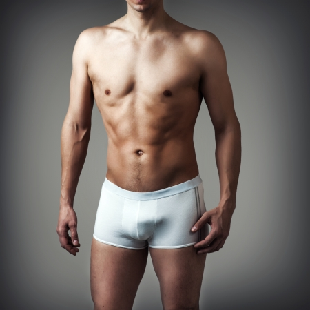 Muscular young sexy handsome man posing in white underwear on gray background photo