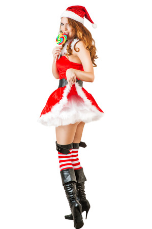 sexy christmas young adult woman wearing santa claus clothes and holding lollipop isolated on white  photo