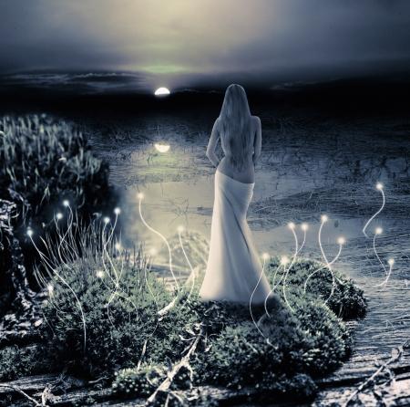 Fantasie magische wereld. Fee of zeemeermin staat op groen eiland in het meer en het letten op de maan Stockfoto