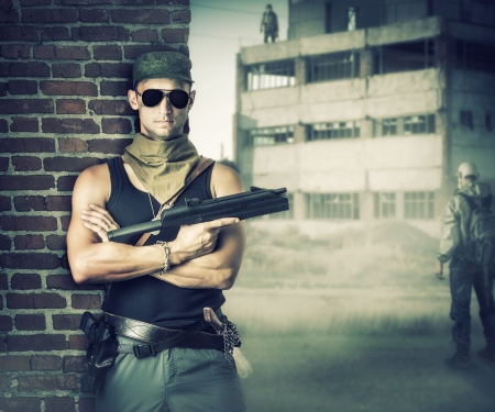 Military man with gun - automatic stay about brick wall in post apocalyptic world photo