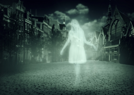 ghostly: white ghost of a woman walking down the street of the old town Stock Photo
