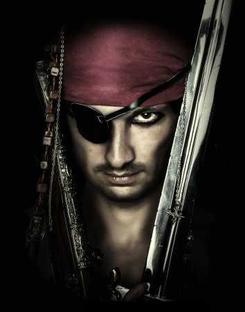 Portrait of handsome male pirate holding sword on black  Stock Photo