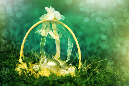 yellow  Basket of golden easter eggs on green grass  photo