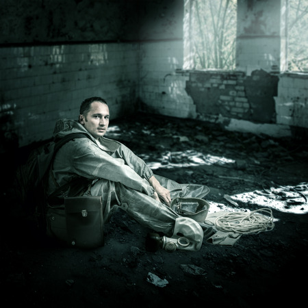 Military man with gas mask sitting on a floor of ruins of buildings in post apocalyptic world
