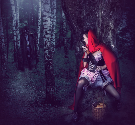 Little Girl Red Riding Hood with automatic in wood sit in ambush behind a tree