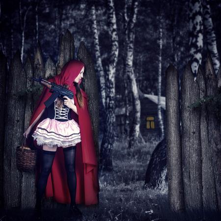 caperucita roja: Niña Caperucita Roja con cambio automático en estancia de madera en una emboscada detrás de una valla