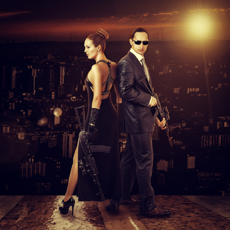 hitman: Fashion photo of young beautiful couple - man and woman snipers holding automatics outdoor