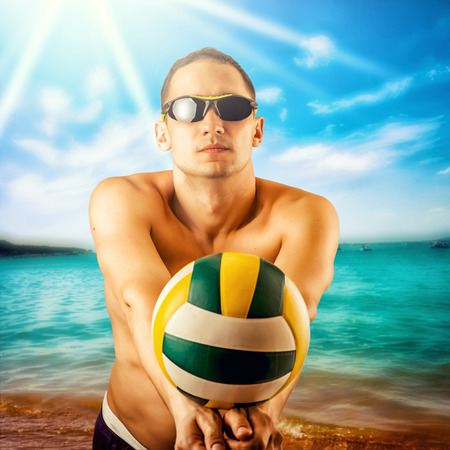 beach volleyball: attractive young man playing volleyball on the beach summertime
