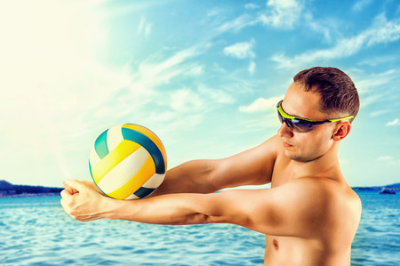 attractive young man playing volleyball on the beach summertime photo
