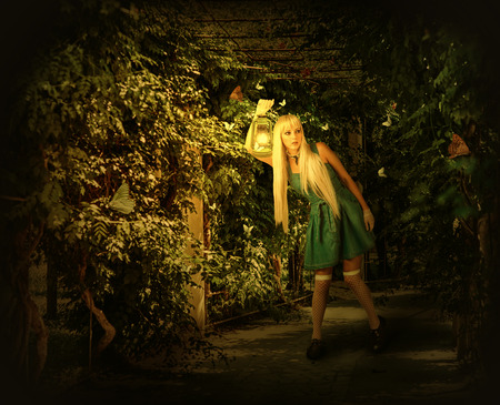 Young blond woman in dress walking on a mysterious path into an enchanted forest. She holding kerosene lamp Reklamní fotografie