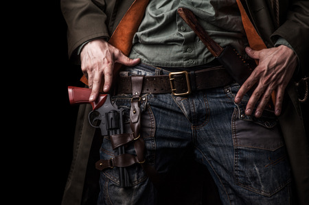 Male hands cowboy and a revolver on his belt on black background