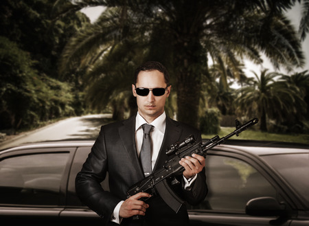 Confident bodyguard wearing sunglasses while standing against limousine and holding automatic