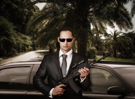 Zuversichtlich Bodyguard mit Sonnenbrille im Stehen vor Limousine und hält die automatische