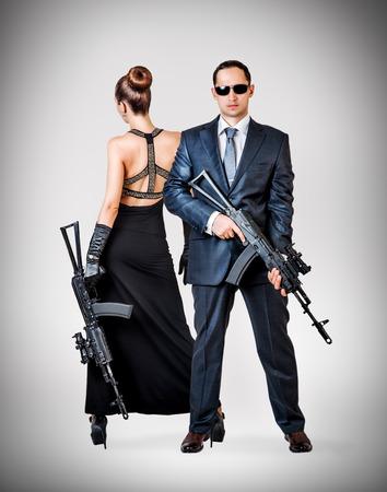 slayer:  Fashionable couple - woman and man holding automatics on gray background