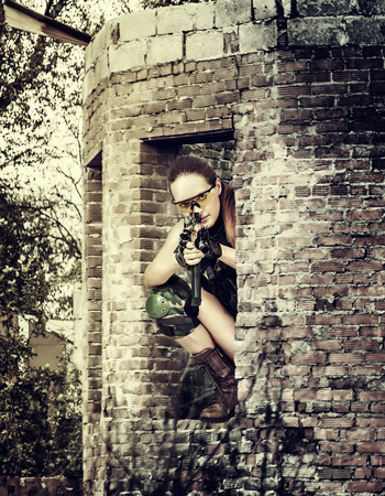 Young woman sniper sitting in ruins with automatic  Stock Photo - 30114724