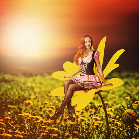 Beautiful sexy woman pixie sitting on a yellow flower at summer Stock Photo - 30152650
