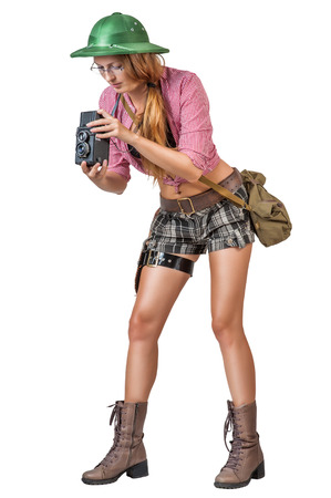pith: Young woman traveler wearing glasses  in retro style holding vintage camera isolated on white background Stock Photo