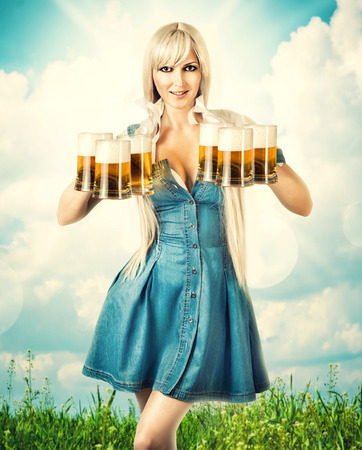 young sexy oktoberfest woman wearing a dirndl holding six beer mugs. outdoor background with grass and sky photo