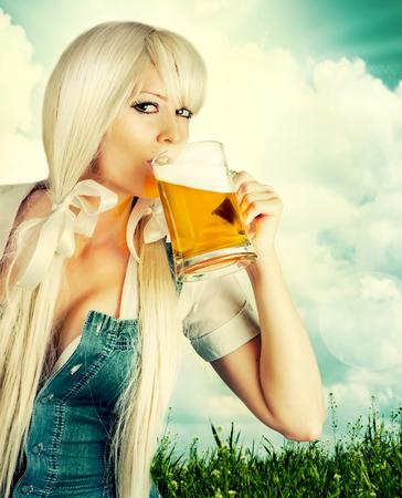 美しいオクトーバーフェスト セクシーを着た若い女性ギャザー スカートのビールを飲むからマグカップ屋外