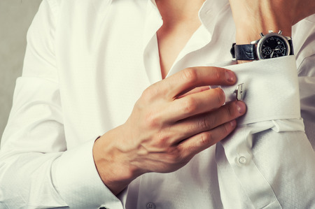 man buttons cuff-link on French cuffs sleeves luxury white shirt. Tonal correction