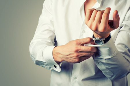 Sexy man buttons cuff-link on French cuffs sleeves luxury white shirt. Tonal correction 写真素材