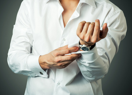 french cuffs: Sexy man buttons cuff-link on French cuffs sleeves luxury white shirt Stock Photo