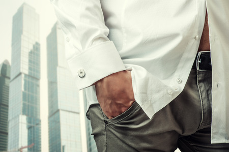 Mans hand in a white shirt with cufflinks in a pants pocket closeup. Tonal correction photo