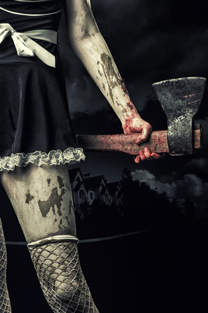 Horror. Dirty woman's hand holding a bloody ax outdoor in night town