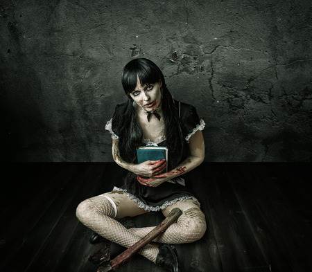 Horror. Dirty womans hand holding book and a bloody ax sitting on a wooden floor in old house photo