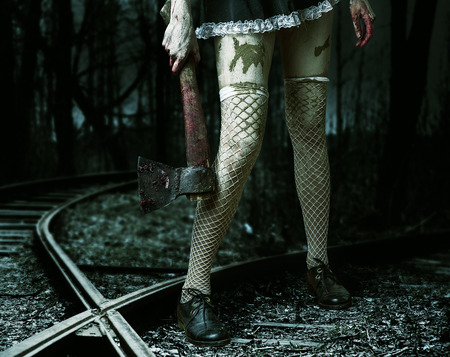 Halloween horror. Dirty womans hand holding a bloody ax outdoor in forest photo