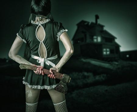 ハロウィーン ホラー。汚れた女性戻って血まみれの斧を持って立っている、屋外の古い家を見て 写真素材