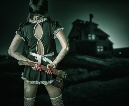 Halloween horror. Dirty woman stands back holding a bloody ax and looks at the old house  outdoor photo