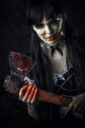 extends: Dead female zombie with bloody axe extends hand to shot. Halloween horror. Evil ghost with black eyes