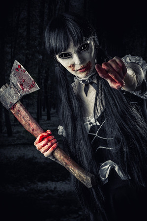 woman zombie with bloody axe extends hand to shot and pointing at you. Halloween concept. Evil ghost in night forest photo