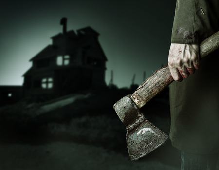 murderer: Axe with blood in male hand.  murderer or butcher looking on a night house, halloween theme
