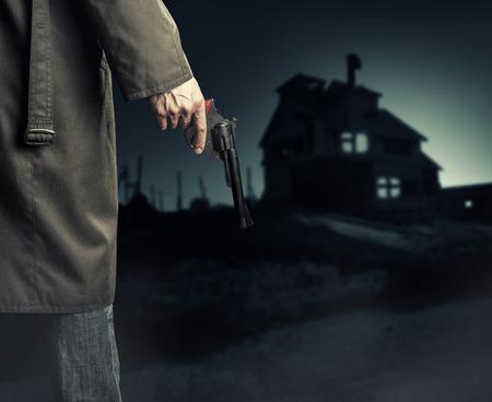 hand gun: Male Hand with gun (revolver) outdoor.  Man killer looking on night house Stock Photo