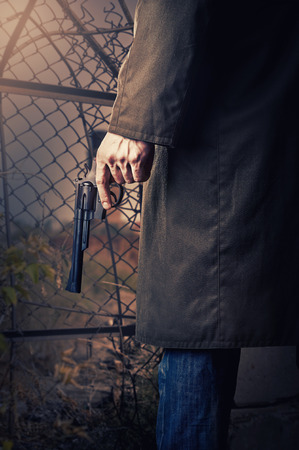 Male Hand with gun (revolver) outdoor. Stock Photo
