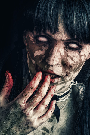 Scary zombie woman  with white eyes and bloody hand photo