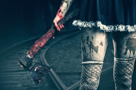 Horror. De hand van vuile vrouw die een bloedige bijl outdoor in nacht bos Stockfoto