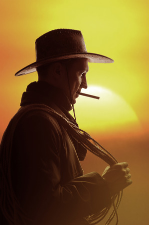 cowboy in hat with cigar and lasso silhouette photo